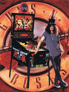 1994 Guns N' Roses Flyer by DataEast/Sega -  Features Flippers (3), Pop bumpers (3), Ramps (2), Multiball (6), Captive Ball (1), Automatic Plunger, Manual plungers (2, one gun-shaped, one rose-shaped], Game-controlled magnets. The captive ball area is delineated in part by one side of a pop bumper. The guns ramp has a diverter that can route the ball into the Snake ramp (to be served by the Rose-shaped plunger) or to the left flipper.