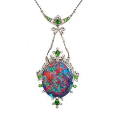 Birthstone of October, colour-changing opals are one of the most widely loved gems by antique jewellery aficionados and modern jewellery designers alike.  A La Vieille Russie antique black opal pendant set in a platinum mount with demantoid garnets and diamonds, American, circa 1915.