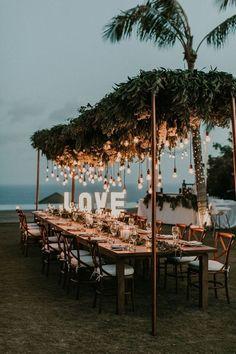 Varal de lâmpadas | Casamento iluminado é casamento ainda mais bonito e feliz! As luzinhas são tendência na decoração e aparecem em vários estilos de festa. Você gosta da ideia? Aproveite para se inspirar! Aqui, mesa comunitária decorada com varal de lâmpadas. #wedding #casamento #weddingdecor #decoracaodecasamento #lights #varaldelampadas #modernwedding #tablescapes #mesaposta