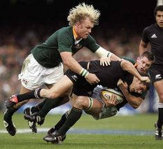 New Zealand fly-half Dan Carter is hauled to the ground by Joe Van Niekerk and Schalk Burger of South Africa, South Africa v New Zealand, Tri Nations, Newlands, August 6 2005.