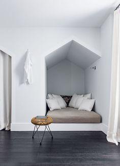 Dans la chambre, les murs couleur Pavilion Blue (Farrow & Ball) et les plinthes blanches qui encadrent la cabane et, à gauche, l'entrée de la salle de bains, rappellent les cabines de plage. Tabouret en bambou (Compagnie française de l'Orient et de la Chi