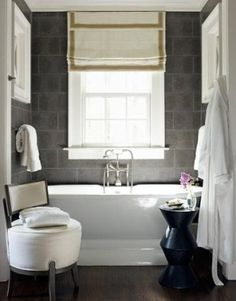 Small black and white bathroom with gray slate tile and free standing tub.