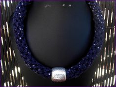 Collar trenzado en trapillo azul estampado con abalorio plateado. El collar se remata con terminales y  broche tipo mosquetón.