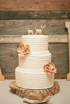 A three-tiered, white buttercream wedding cake with metallic flowers and a rustic deer topper by Corner Space Cakes   Brides.com