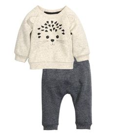 CONSCIOUS. Set in sweatshirt fabric with a soft, brushed inside. Top with printed design and attached appliqués at front, long raglan sleeves, snap fasteners at back of neck, and ribbing at cuffs and hem. Pants with elasticized waistband and ribbed hems. Cotton content is organic.