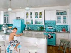 I LOVE THE COLOR!!! The punchy turquoise hue of the vintage-style appliances puts a chic spin on this coastal kitchen. A tumbled-glass backsplash mimics natural sea glass and contrasts sleek concrete countertops.