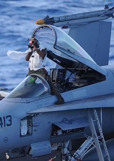 US Navy F-18E Super Hornet plane captain taking a picture of deck operations.