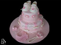 Pink baby girl shower cake with all edible hand-made fondant toppers (booties, rattle, bib and pacifier).