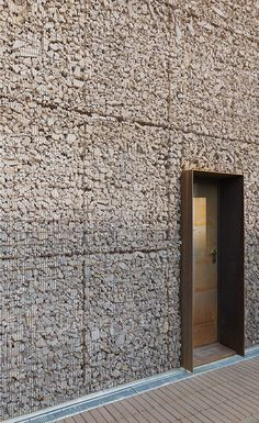 Six 3-storey terrace houses clad and roofed with Corten steel gabions filled with crushed brick and cobblestones reclaimed from the demolition of the barn that previously stood on the site in Sesto San Giovanni, Milan, Italy.