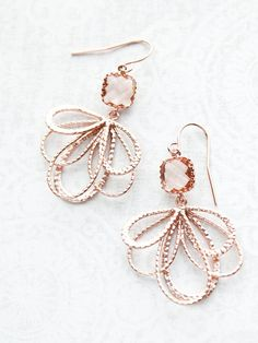These are beautiful modern rose gold floral filigree dangle earrings. The square peach champagne glass stones are set in rose gold plated brass crown settings and from the bottom of these jewel drops hangs a pretty floral looping filigree. These are rose gold plated brass lacy