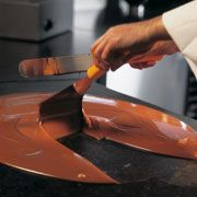 Step 3: Keep the chocolate moving by stirring continually with a spatula and a scraper.