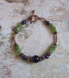 Beautiful handcrafted 7+3/4inches long Bracelet made with genuine natural semiprecious stones of 10mm and 6mm round Amethyst, 5mm rondelle cut natural Peridot, 4mm solid Copper daisy spacers, 5mm solid Copper bali beads, 20mm solid Copper tube beads, with a Copper toggle clasp closure.