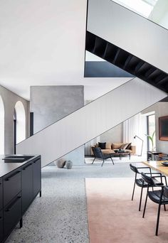 The modern steel staircase adds a striking architectural element to the space and leads from the ground-floor living spaces to the bedrooms upstairs. Tagged: Living Room, Terrazzo Floor, Sofa, Pendant Lighting, and Chair. Hotel Concept, Arched Doors, Modern Staircase, Staircase Ideas, Terrazzo Flooring, Higher Design, Architectural Elements, Architectural Digest, Black Kitchens