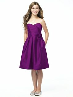 Dessy Collection Junior Bridesmaid style JR 504 is the Junior version of style D496. Strapless cocktail length dupioni dress with sweetheart pleated surplice bodice. Matching belt and flower detail at natural waist. Pockets at side seams of full pleated skirt. Also available full length as style JR505.
