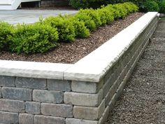 Unilock Olde Quarry Sierra retaining wall with Bedford limestone cap with rock faced edges