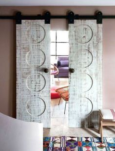 textured barn doors - incised circles in whitewashed vintage barn doors - Basset Images via Atticmag