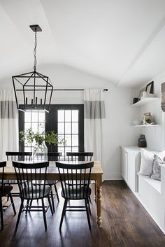 Black and white dining room. White walls and black doors. Built in window seat. Wall color: white dove by Benjamin Moore. Door color: iron ore by Sherwin Williams. Black And White Dining Room, White Rooms, White Walls, White Dining Room Table, Lights Over Dining Table, Black Dining Room Furniture, Pine Dining Table, Black Dining Room Chairs, Black Chairs