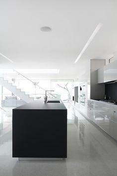 Gran parte de la planta superior está dedicada a la suite principal. Mínimamente amueblado en blanco y negro, el dormitorio está situado en el lado oeste de las vistas del océano y mantiene el máximo calor por una chimenea. Paredes de ventanas del piso al techo envuelven la esquina y un generoso balcón ofrece un espacio para descansar y observar las mareas. Una ventana interior se ve en el espacio de la escalera y para el lado opuesto de la casa.