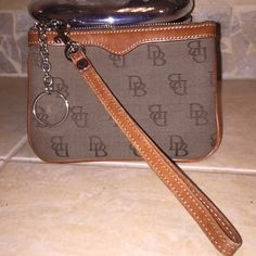 Vintage Dooney & Bourke Wristlet & Keychain Vintage Dooney & Bourke canvas & leather wristlet with a key chain.  Safely carry your driver's license, credit card, cash & keys, yet small enough to tuck in your pocket!!! Dooney & Bourke Bags Clutches & Wristlets