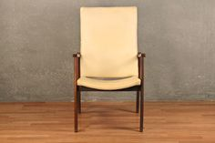 Attractive danish modern high back armchair featuring an ivory vinyl upholstery. Would add style and charm to any space. In overall good condition with some minor wear and discoloring. Disclaimer: This piece is not available...