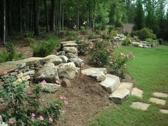 A beautiful natural stone wall built in and around the boulders ties the two features together with Perennial shrubs in front of the wall adding to the flow and unity. Picture compliments of www.nichegardenslandscaping.com