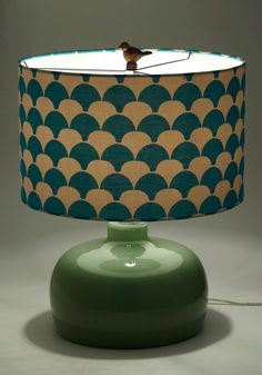 Set your distinguished decor apart from other abodes by adding this exquisite table lamp to your sophisticated design scheme. Flaunting such fetching details as a domed, sea-green glass base, a cylindrical shade printed with playful fans of deep teal and light cream, and a bronze bird finial, this peerless piece will set your flat aglow with warm, wonderful light.