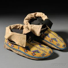 Pair of Plains Cree Beaded Buffalo Hide Man's Moccasins, c. last quarter 19th century, with multicolored geometric and cross designs on a yellow and pumpkin background, with horse track designs at the heels, with blue trade cloth tongues and trim, remnant red trade cloth, lg. 10 in.