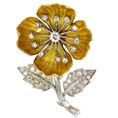 A Boucheron Brooch, a center spray of 12 round-cut diamonds rest on shimmering, yellow-gold enamel petals mounted in 18K gold.