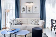Prosta kanapa, współczesne grafiki na ścianie oraz designerskie stoliki kawowe tworzą nowoczesny wystrój tego salonu. A przytulności wnętrzu dodają błękitne zasłony w oknach. Półprzejrzyste firanki zapewniają dyskrecję i dopływ dziennego światła.
