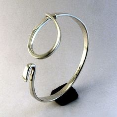 A solid sterling silver latch bracelet that is usually slipped on, when opened, over the hand much like a bangle, then latched. The soft contour of