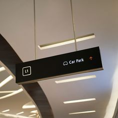 Overhead directional signage in stainless steel and back lit, matte black acrylic.