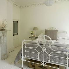 This pretty bedroom has an iron bed, glassware and white painted floorboards to create a serene bedroom scheme.  #Sleeptember