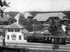 Schwarz-weiss-Bild mit Zügli neben altem Bahnhof, im Hintergrund Bauernhäuser