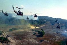 US Army Hueys fly towards a landing zone marked by yellow smoke.