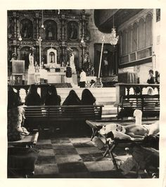 1944- Worshippers gather at the front of a cathedral on the island of Leyte as Mass is celebrated, while American soldiers are treated for wounds in an emergency hospital set up in the rear of the house of worship.