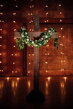 The cross will be draped with a greenery garland with pops of blush rustic cross flower garland rose garland ceremony backdrop venue the wareham junglespirit Image collections