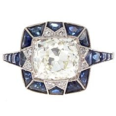 The provenance and allure of the Art Deco time period has inspired the creation of this one of a kind engagement ring. Designed with superior craftsmanship that is hardly replicated today. Featuring a 2.38 carat old cushion cut diamond that is K-L color, VS+ clarity. Perfectly complimented by a halo of specially cut royal blue vibrant sapphires. Hand crafted in platinum.  Ring size 4-3/4 and may be resized.