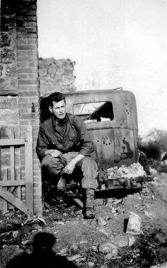 Un GI est assis sur le pare choc arrière d'une épave de KZ 4 Renault (sans la malle) à côté d'une maison en ruine.  A noter en bas à gauche l'ombre du photographe.