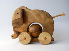 Ellie Elephant Wooden Pull Toy.  Made entirely of wood and coated with baby-safe flax oil.  Rotating ball, ears move while walking.  Seller has other designs available, charming!  toporko, Etsy.  $40.00