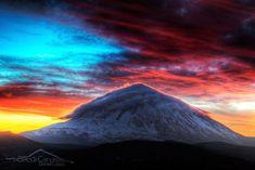 Un gorro de nubes cubre el Teide nevado en una puesta de sol que ilumina el cielo de vivos colores, justo después de una tormenta. Fotografía de Daniel Lopez