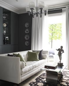 (I like the color scheme) crisp white silk drapes curtains, white leather tufted modern sofa, stainless steel coffee table with glass top, decorative vertical black & white plates wall art, rug, white drapes, built-ins shelves cabinets, black vase, frosted glass light fixture and crown molding! white black charcoal gray living room space colors....KJB
