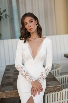 We've found the perfect A-line wedding dress with sleeves and a train. This minimalistic gown from Mila Bridal is made from stretchy crepe and delicate soft lace. The neckline and slit can easily be altered to your wishes. #weddingdress #lacedress #longsleeveweddingdress #simpleweddingdress