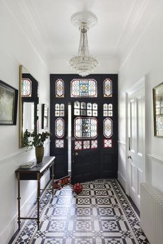 This modern hallway is flooded with light thanks to the stained glass in the door, which perfectly compliments the tiled floor in this stunning urban home. The modern hallway design is complemented with framed pictures and a statement light feature. House Design, London Townhouse, Victorian Townhouse, House Interior, Modern Hallway, Home, Interior, Elegant Homes, Elegant Home Decor