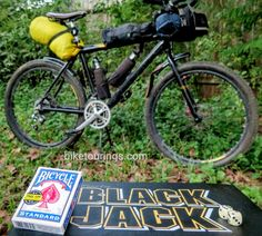 Picture of bicycle playing cards, black jack and dice with mountain bike for bicycle touring in background