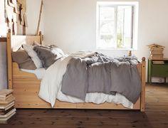 환하게 햇빛이 비추는 침실의 마루 위에 놓여있는 소나무 원목 침대프레임과 침대협탁