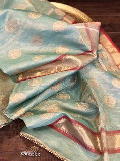 Code: Type: Tissue Chanderi Katan SilkColor: Light Firozi, Res, Golden Zari Design : Zari woven oval Buta all over body, Red border and Pallu with antique Zari workBP: Yes, running