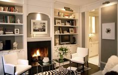 Paul Davis New York: Gorgeous built-in bookshelves surrounding fireplace with sconce lighting. A pair of ...