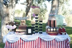 French vintage take on the traditional circus theme. Michelle from Social Event Planning Co used red and black to show off thick striped and polka dot patterns. Sweet treats included circus staples such as red candy apples, cotton candy and lollipops, as well as donut pops and Bakerella-inspired cake pops. We love the popcorn topiaries and think they were the perfect show-stopper for this Circus table.