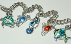 Beautiful rhodium plated (won't tarnish) sterling silver enameled ocean love, charm bracelet, by Nicole Barr available @ Countryman's Village Jewelers