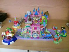 Polly Pocket: Disney Castle playset. This figgen thing was a pretty big playset for the teeny weenie dolls that came inside. I didn't have the two extra expansions, but it sure was a nice toy.